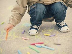 Little boy drawing with sidewalk chalks. Shallow depth of field
