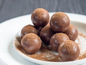 Chocolate balls, cocoa powder on a white plates. Wooden rustic table.