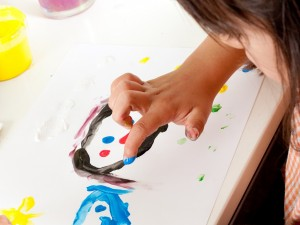 Little girl painting happy faces with fingers